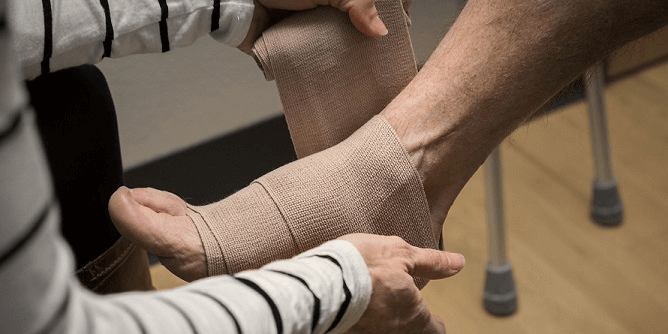 An orthopedic surgeon wrapping an ankle injury.