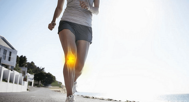 A woman jogging on the beach ith her knee highlighted.